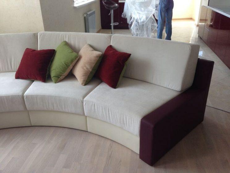радіусний диван з подушками