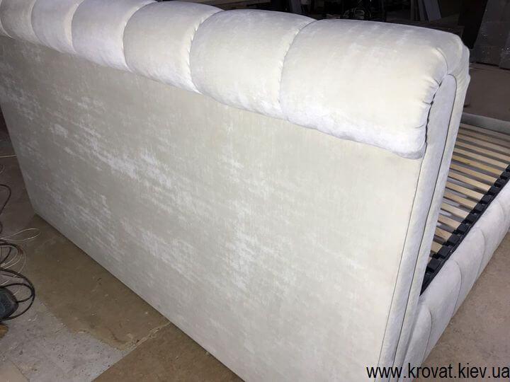 сзади кровать обита тканью